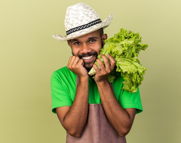 Sorridente giovane giardiniere afro-americano che indossa un cappello da giardinaggio che tiene insalata isolata sul muro verde oliva