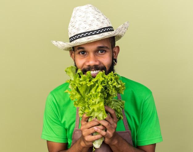 Smiling young gardener afro-american guy wearing gardening hat holding salad