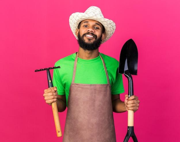 ピンクの壁に分離された熊手とスペードを保持しているガーデニング帽子をかぶって若い庭師アフリカ系アメリカ人の男を笑顔