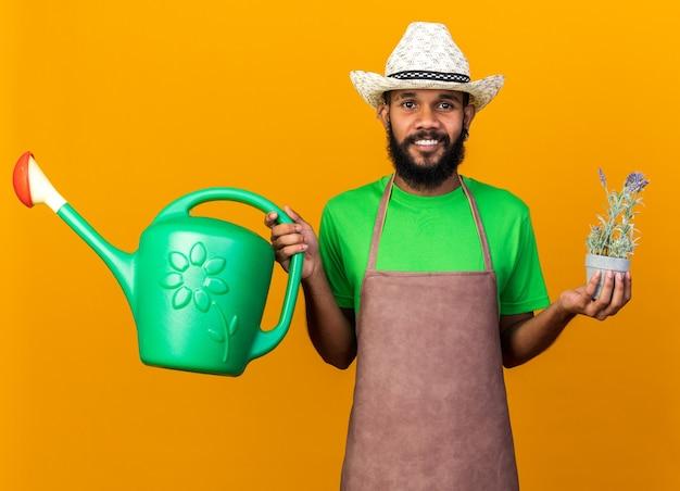 植木鉢の花とじょうろを保持しているガーデニングの帽子をかぶっている若い庭師のアフリカ系アメリカ人の男を笑顔