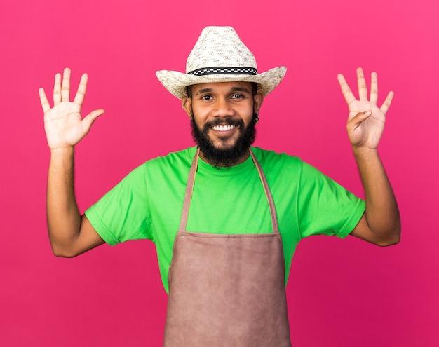 異なる数を示すガーデニングの帽子をかぶっている若い庭師のアフリカ系アメリカ人の男を笑顔