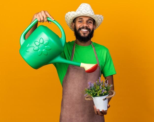 Sorridente giovane giardiniere afro-americano che indossa cappello da giardinaggio che innaffia il fiore in vaso di fiori con annaffiatoio