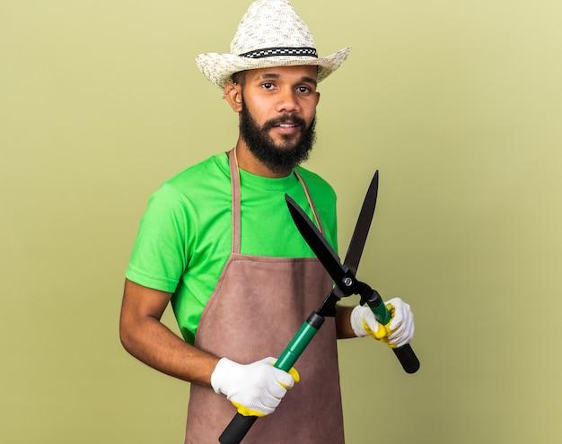 クリッパーズを保持している手袋とガーデニングの帽子をかぶって若い庭師のアフリカ系アメリカ人の男を笑顔