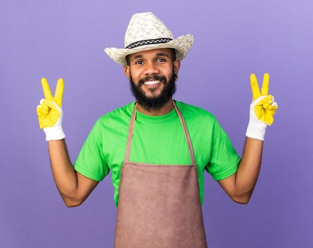 푸른 벽에 격리된 평화 제스처를 보여주는 장갑을 끼고 원예용 모자를 쓰고 웃고 있는 젊은 정원사 아프리카계 미국인 남자