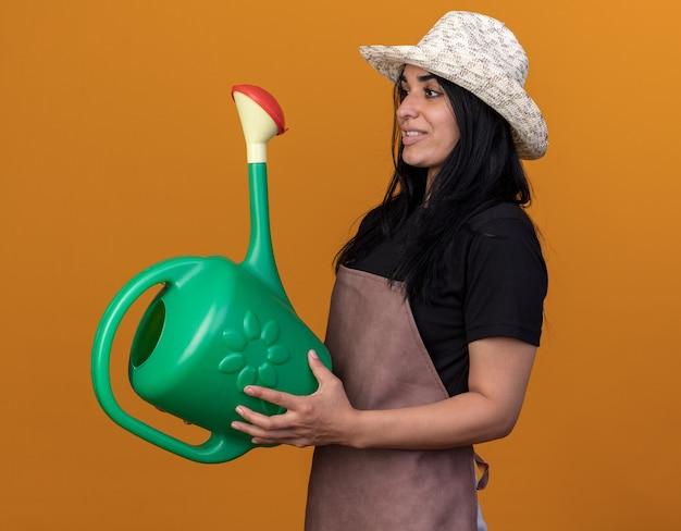 Улыбающаяся молодая девушка-садовник в униформе и шляпе с лейкой смотрит прямо на оранжевую стену