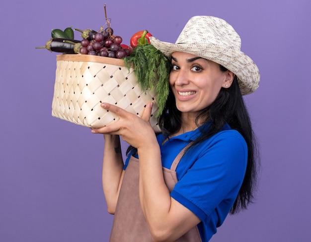 Улыбающаяся молодая женщина-садовник в униформе и шляпе, стоящая в профиле, держит корзину с овощами, глядя вперед, изолированную на фиолетовой стене