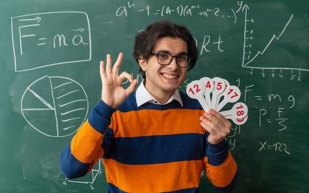 Sorridente giovane insegnante di geometria con gli occhiali in piedi davanti alla lavagna in aula tenendo il numero di fan guardando davanti facendo segno ok
