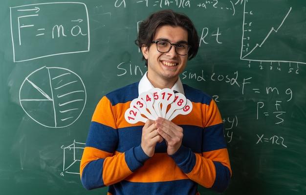 Sorridente giovane insegnante di geometria con gli occhiali in piedi di fronte alla lavagna in aula tenendo il numero di fan guardando front
