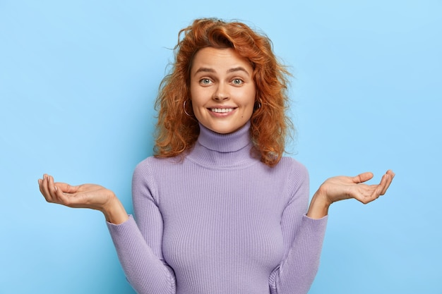 Smiling young ginger female makes questioned gesture, spreads hands sideways