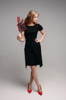 Smiling young girl in black dress keeping branch in hand