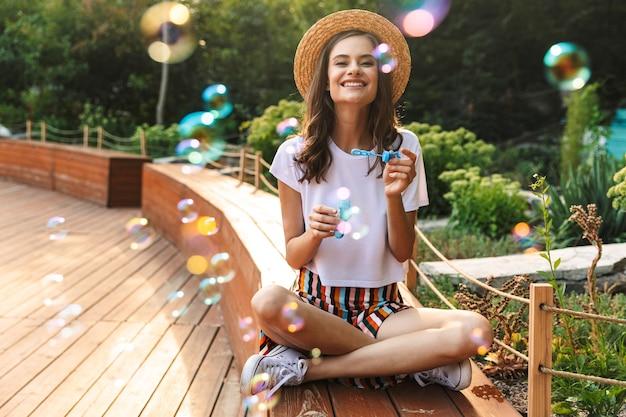 屋外の公園でシャボン玉を吹く笑顔の若い女の子
