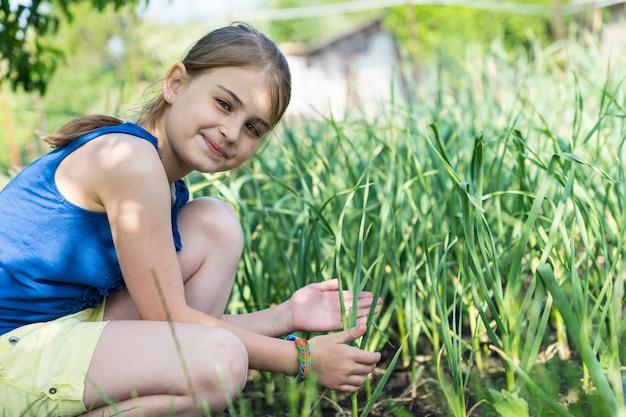 小さなホールディングで菜園でタマネギの植物をチェックし、優しい笑顔でカメラを見ている若い女の子の笑顔
