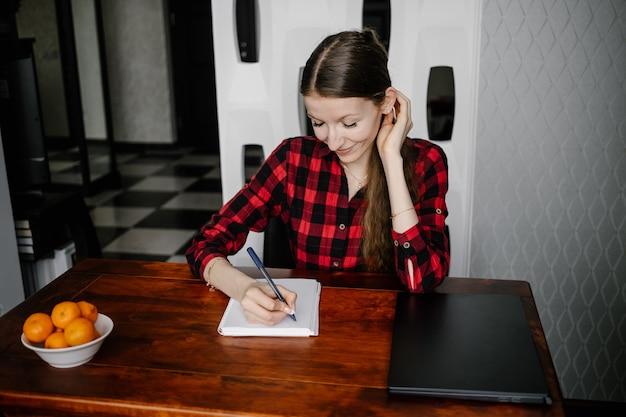 宿題をしている笑顔の若い女の子が家のノートに書き込みます