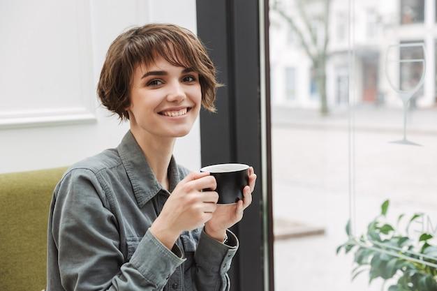 Улыбающаяся молодая девушка пьет кофе, сидя за столиком в кафе в помещении