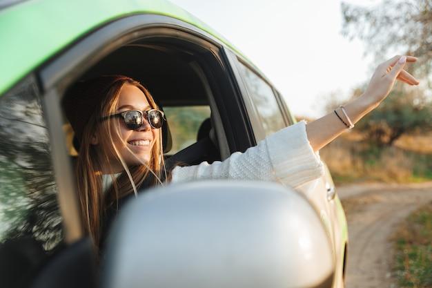 창을보고 일몰 동안 차를 운전하는 어린 소녀 미소