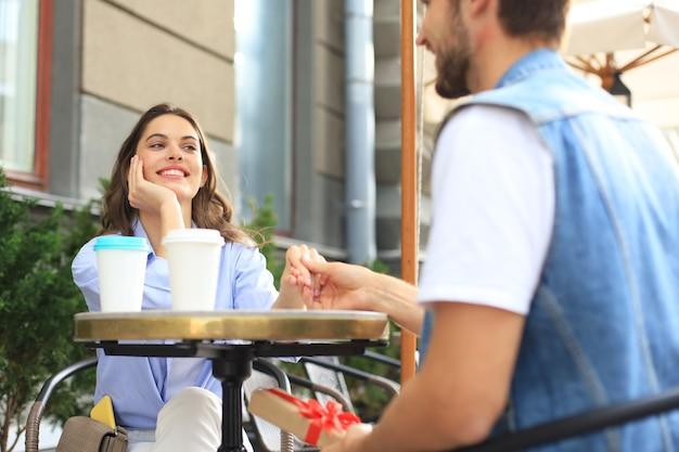 Улыбающаяся молодая девушка, имеющая свидание со своим парнем в кафе, мужчина, держащий настоящую коробку.