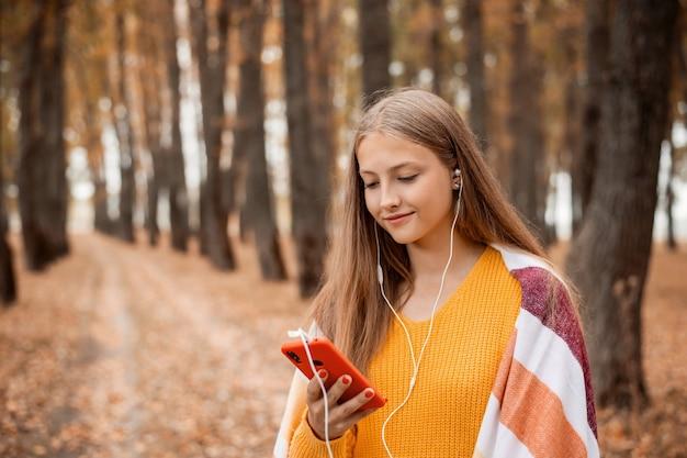 公園を散歩し、音楽を聴いて笑っている少女