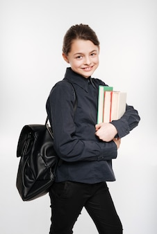 Smiling young girl holding books