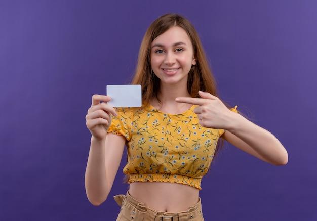Sorridente ragazza giovane azienda carta e indicandolo sulla parete viola isolata