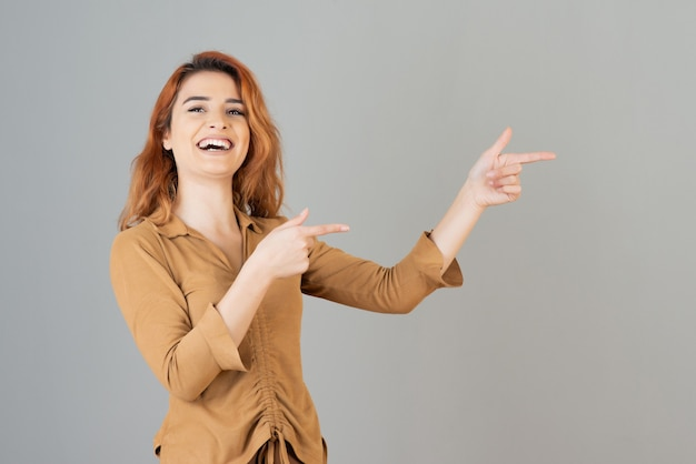 Улыбающаяся молодая девушка держит пальцы вверх и смеется в серой стене