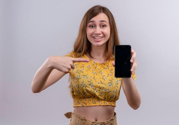 Улыбающаяся молодая девушка держит мобильный телефон и указывает на него на изолированной белой стене