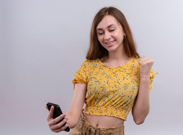 Улыбающаяся молодая девушка держит мобильный телефон с поднятым кулаком на изолированной белой стене