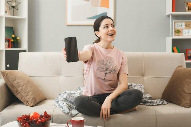Улыбающаяся молодая девушка протягивает телефон, сидя на диване за журнальным столиком в гостиной
