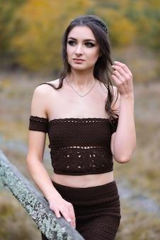 가을 숲에서 아름다운 드레스와 세련된 헤어 스타일에 웃는 어린 소녀