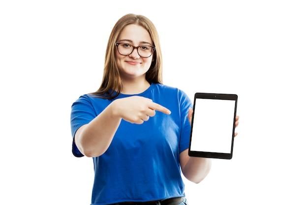 青いタンクで笑顔の若い女の子は、空白の白い画面のタブレットに指を示しています。