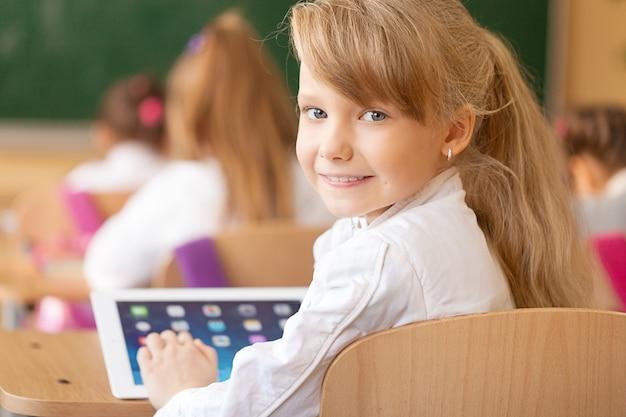 Улыбающаяся молодая девушка в классе с помощью планшета