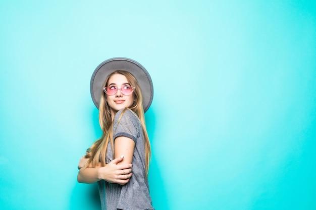 緑の背景に分離されたファッションのtシャツ、帽子、透明ガラスの少女の笑顔