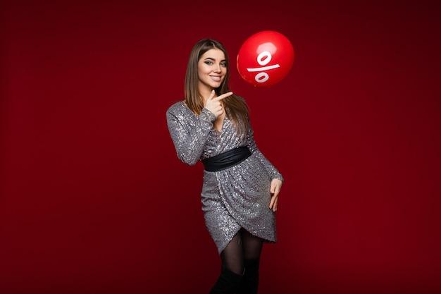 Улыбающаяся молодая девушка в праздничном платье, указывающая на воздушный шар со знаком процента на красном