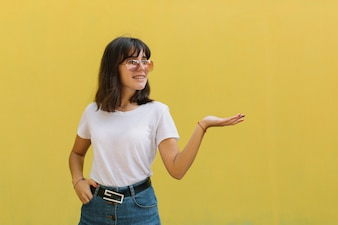 Smiling young girl in glasses and braces while standing alone against a yellow background.