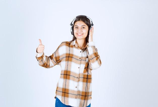 Улыбающаяся молодая девушка в наушниках слушает песню и дает палец вверх.