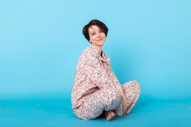 青い背景のスタジオの肖像画に分離された家で休んでいる間ポーズをとるパジャマのホームウェアの若い女の子の笑顔。良い気分のライフスタイルのコンセプトをリラックスしてください。