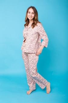 Улыбающаяся молодая девушка в домашней пижаме позирует, отдыхая дома, изолированной на синей стене