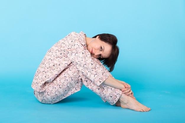 青い壁で隔離の家で休んでいる間ポーズをとってパジャマのホームウェアで若い女の子の笑顔
