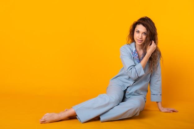 黄色で隔離の家で休んでいる間ポーズをとってパジャマのホームウェアの若い女の子の笑顔