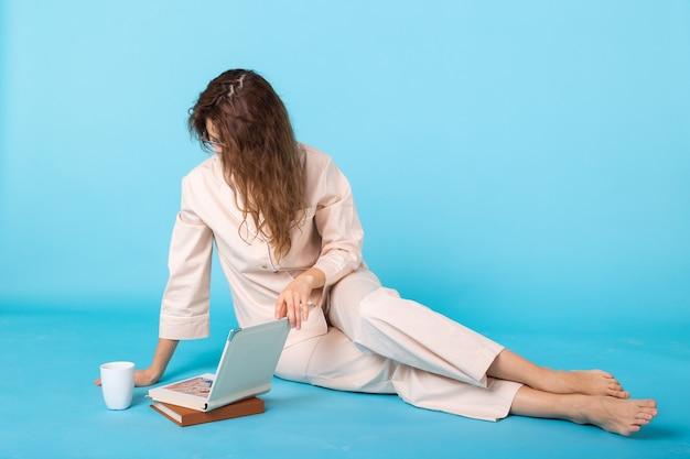 파란색 배경 스튜디오 초상화에 격리된 집에서 쉬면서 잠옷을 입은 웃고 있는 어린 소녀가 책과 함께 포즈를 취합니다. 좋은 분위기의 라이프 스타일 개념을 이완하십시오.