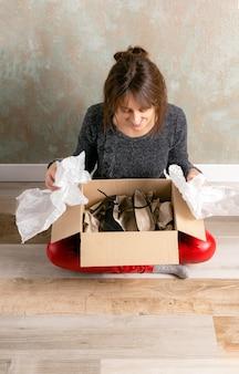 彼女がちょうど黒いハイヒールを含むオンラインで購入したパッケージを開く木の床に座っている赤いズボンの笑顔の若い女の子