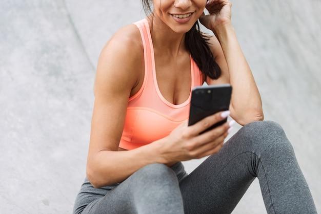 屋外のコンクリートの床に座っている間携帯電話を保持しているスポーツウェアの若い女の子の笑顔