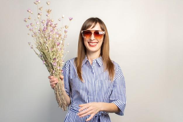 Улыбающаяся молодая девушка в солнцезащитных очках держит букет полевых цветов на светлом фоне