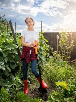 シャベルを保持し、庭で働くウェリントンブーツで若い女の子の笑顔