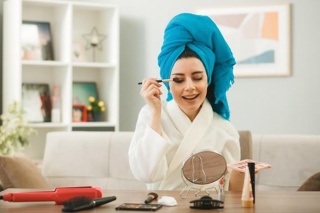 Улыбающаяся молодая девушка смотрит в зеркало, применяя тени для век с кисточкой для макияжа, сидя за столом с инструментами для макияжа в гостиной