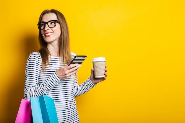 笑顔の若い女の子が目をそらす、携帯電話、コーヒーの入った紙コップ、黄色の背景に購入したパッケージを保持