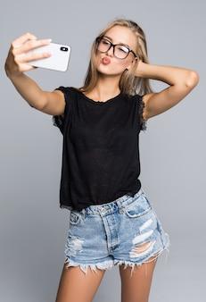 Улыбающаяся молодая девушка делает селфи на смартфоне на сером фоне