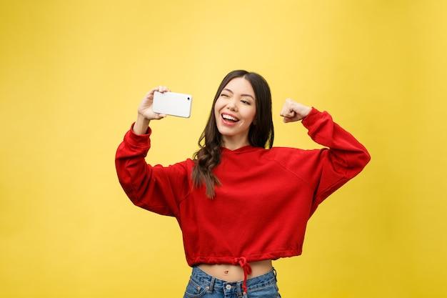 スマートフォンで自分撮り写真を作る笑顔の少女
