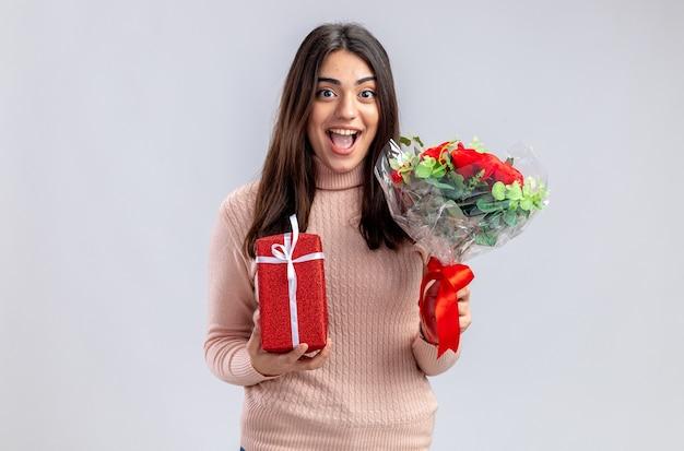白い背景で隔離の花束とギフトボックスを保持してバレンタインデーに若い女の子の笑顔