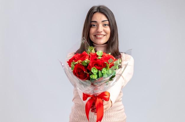 白い背景で隔離のカメラで花束を差し出してバレンタインデーに若い女の子