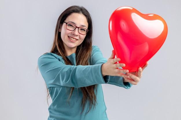 발렌타인 데이에 웃는 어린 소녀 흰색 배경에 고립 된 카메라에 심장 풍선을 들고